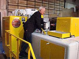 Worker using a specialty cold heading machine
